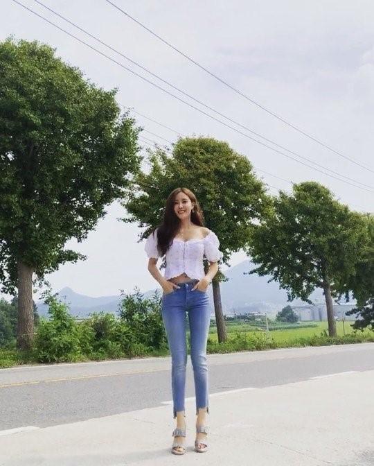 '효민' 블라우스를 입고 길거리에 서있는 모습이다